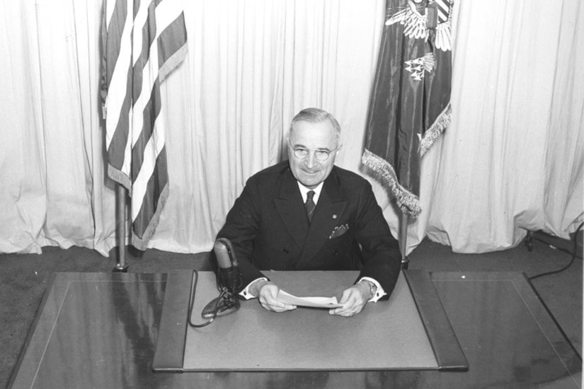 President Harry S. Truman sits behind a desk with a microphone holding papers.