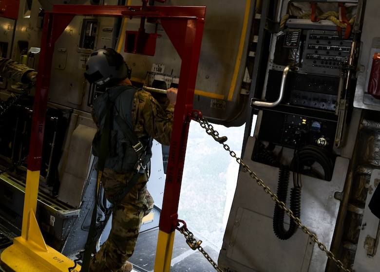 Staff Sgt Johnathan Fishel, a C-17 Globemaster III loadmaster assigned to the 15th Airlift Squadron at Joint Base Charleston, S.C., opens the cargo door in preparation for an air drop over Pope Army Airfield, N.C., Feb. 20, 2020.
