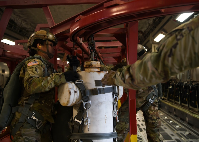 Sgt. 1st Class Katherine Greene, a test parachutist assigned to the Airborne and Special Operations Test Directorate at Fort Bragg, N.C., moves a mannequin to the ready position for an air drop onboard a C-17 Globemaster III over Pope Army Airfield, N.C., Feb. 20, 2020.