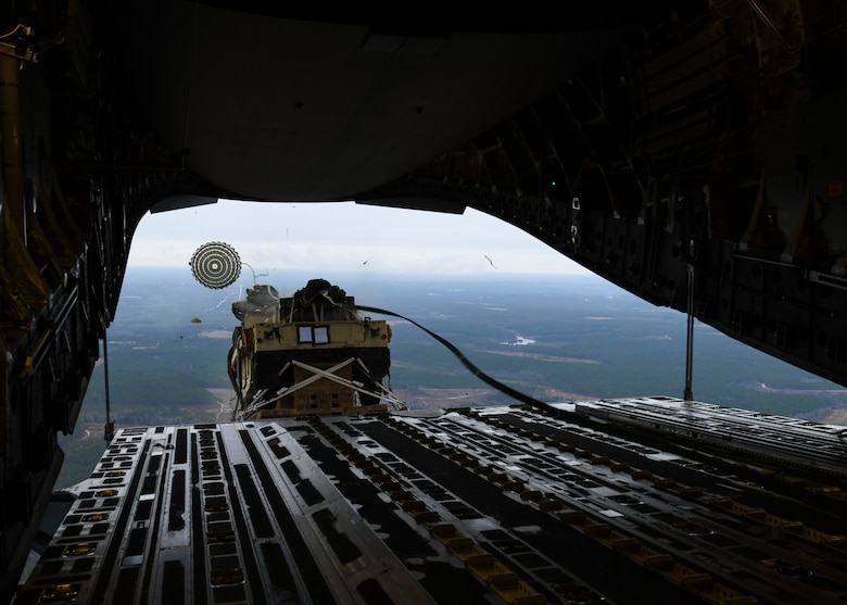 A loadmaster ejects a humvee out of a C-17 Globemaster III over Pope Army Airfield, N.C., Feb. 19, 2020.