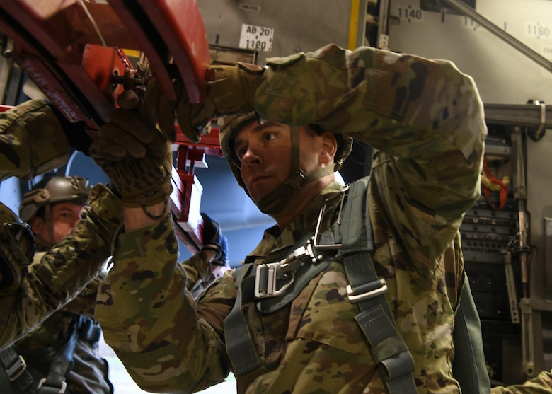 Sgt. 1st Class Jonathan Reed, an operations NCO assigned to the Airborne and Special Operations Test Directorate at Fort Bragg, N.C., prepares a mannequin rack for an air drop mid-flight on a C-17 Globemaster III over Pope Army Airfield, N.C., Feb. 20, 2020.