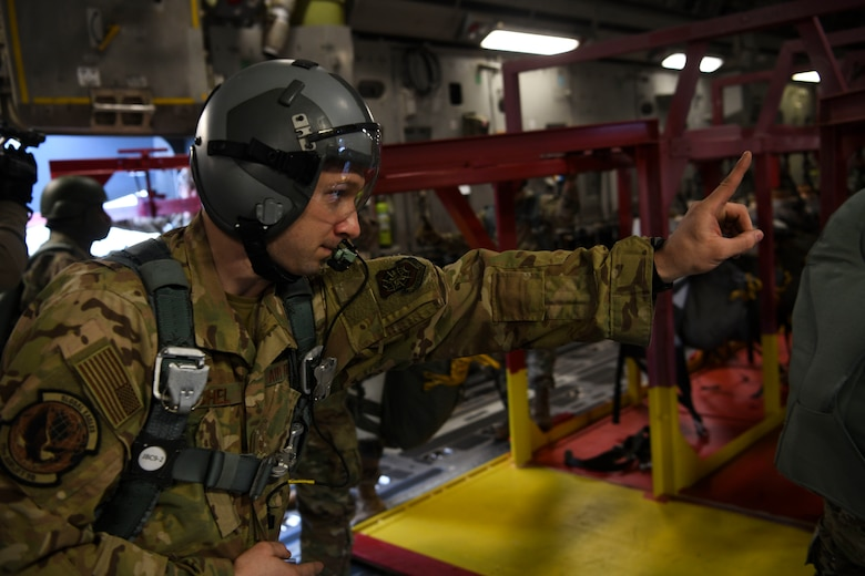 """Staff Sgt Johnathan Fishel, a C-17 Globemaster III loadmaster assigned to the 15th Airlift Squadron at Joint Base Charleston, S.C., gives a jump master the, """"one minute before drop"""" hand sign over Pope Army Airfield, N.C., Feb. 20, 2020."""