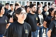 woman wearing black army shirt stands in line with other young people.