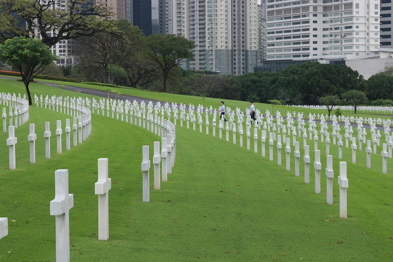 Airmen from Dyess Air Force Base, Texas, walk near the graves of fallen service members at the Manila American Cemetery in Manila, Philippines, Feb. 17, 2020.