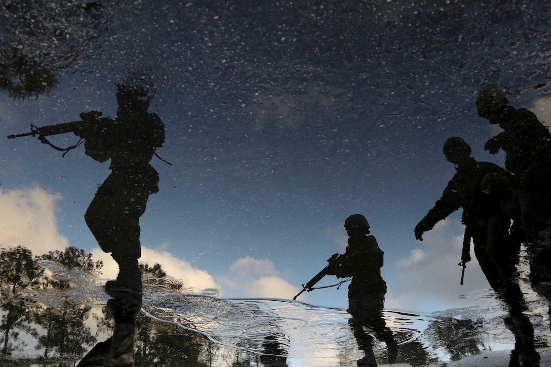 Silhouettes of Marine Corps recruits carrying weapons are reflected in water.