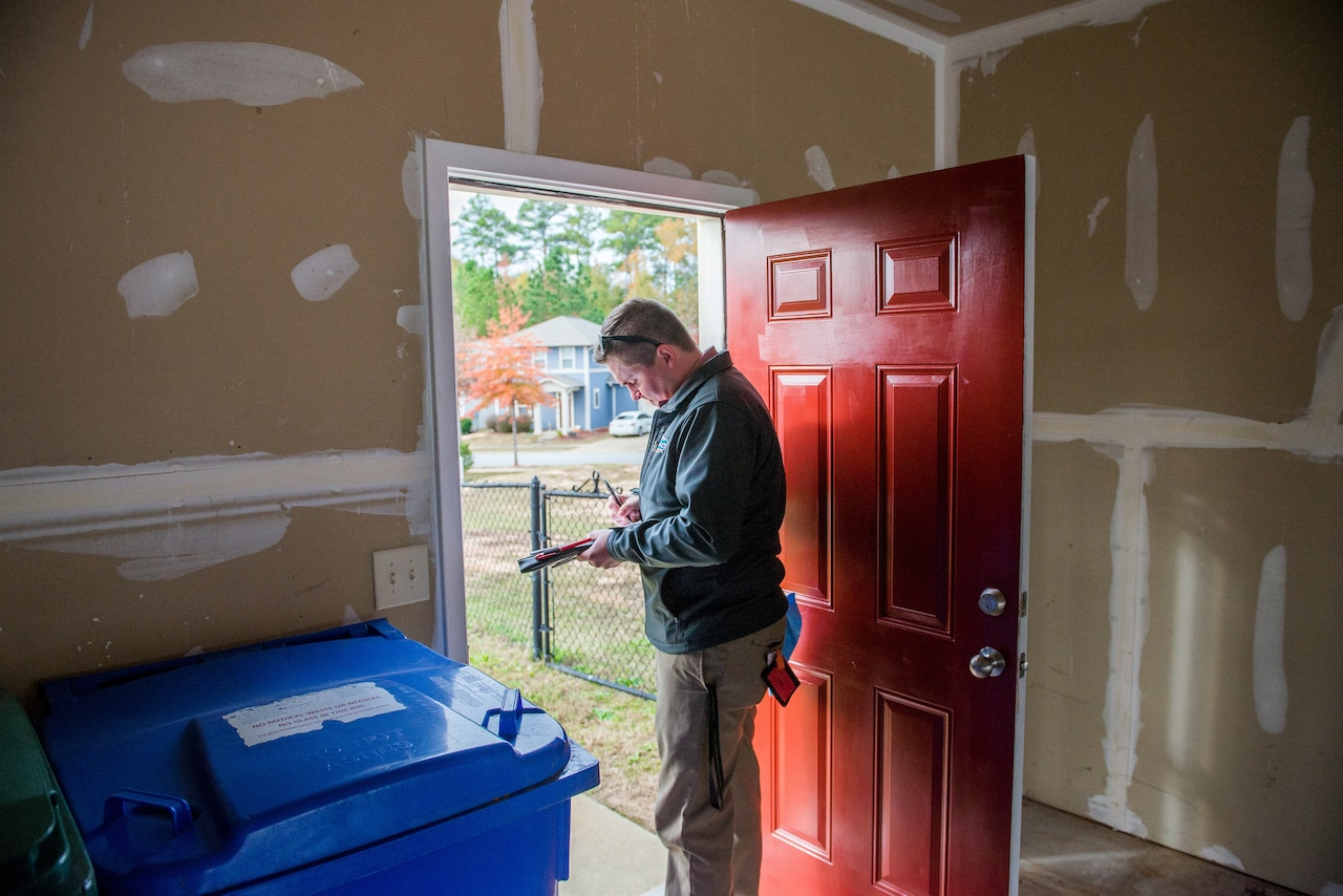 A man makes notes on a clipboard while standing in a doorway.