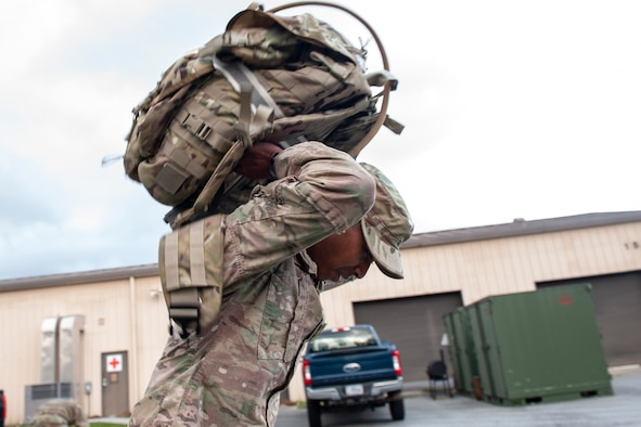 A photo of an Airman putting a ruck sack into a van.