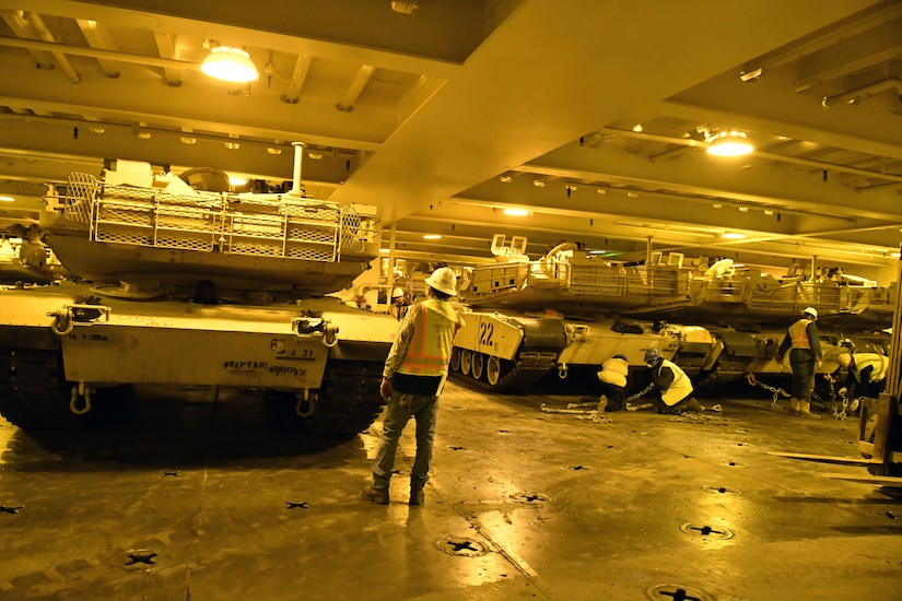 Workers secure tanks in hold of ship.