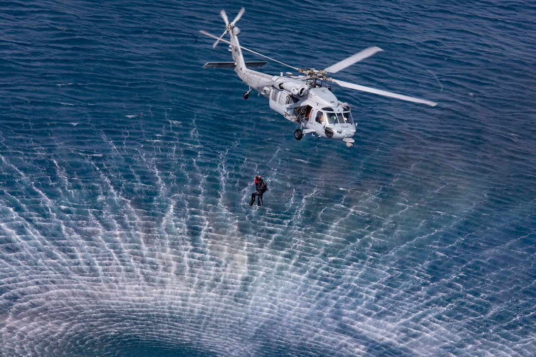 Two sailors hang on a line from a helicopter hovering over water.