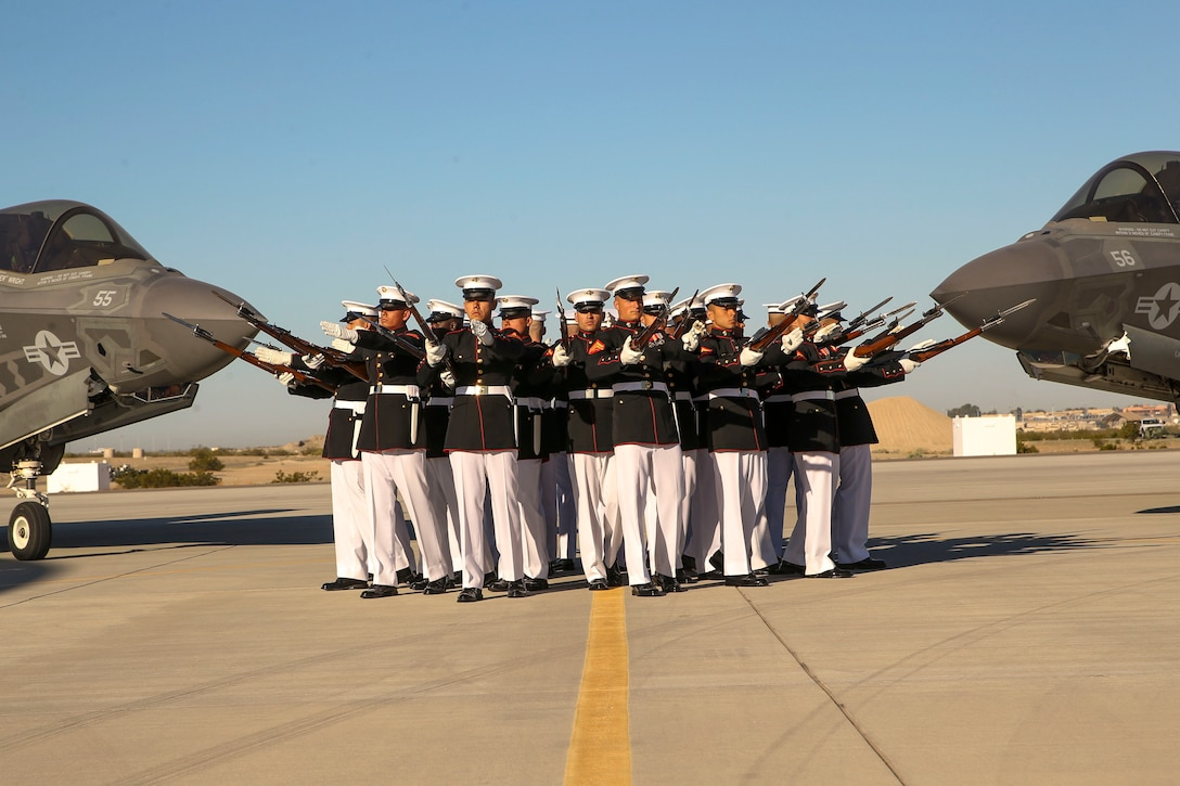Marines gather in a circle with weapons in between two aircraft.