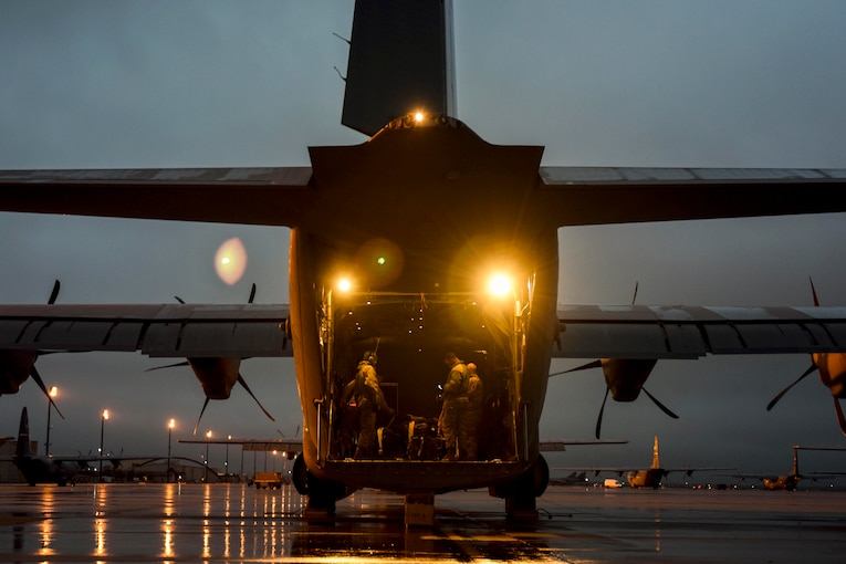 Airmen stand in an aircraft parked on a runway.