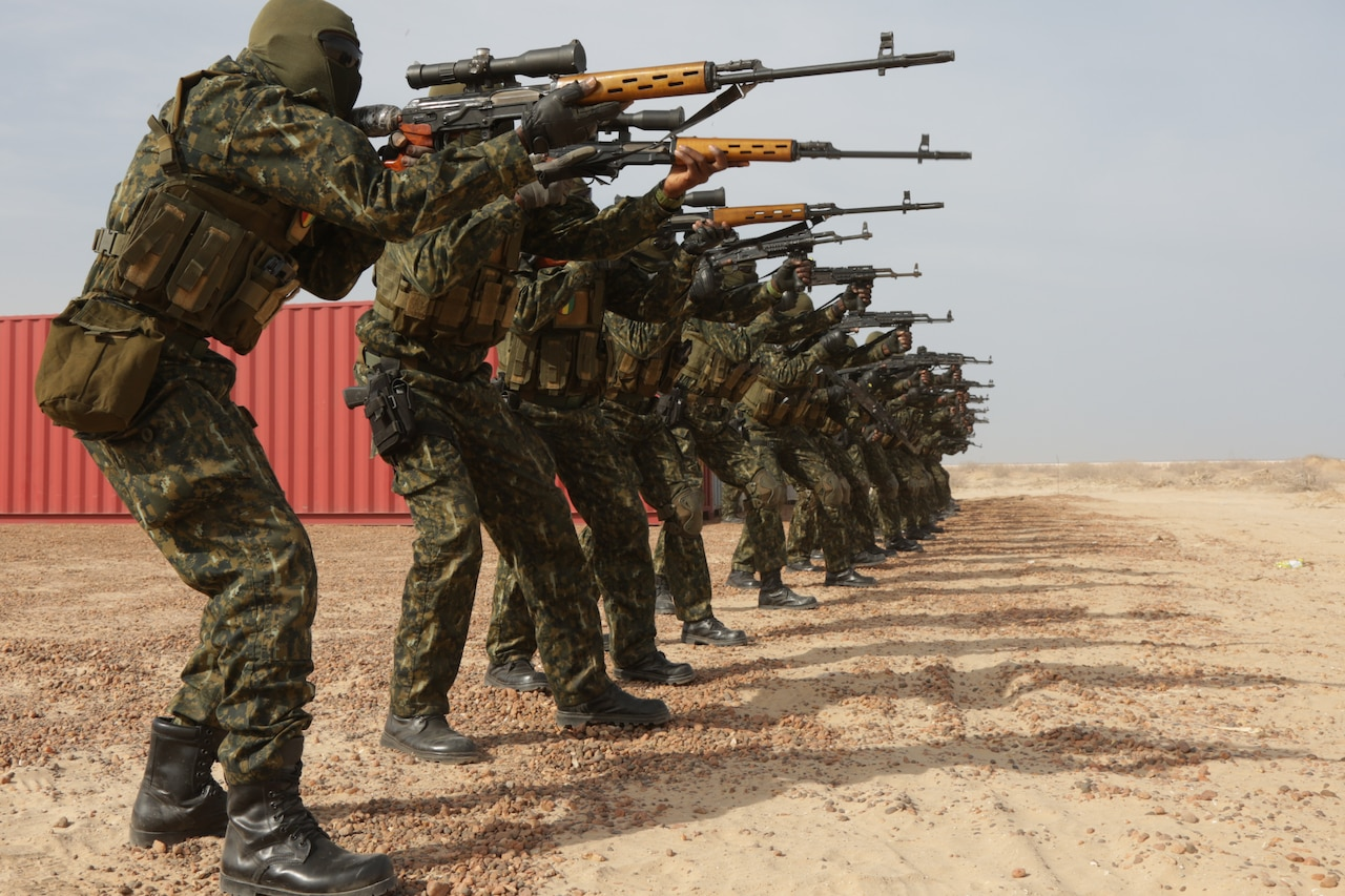 Line of soldiers fire weapons.