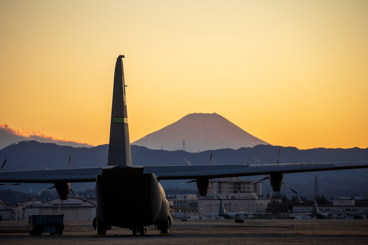 Aircraft sits on runway with Mount Fuji in background.