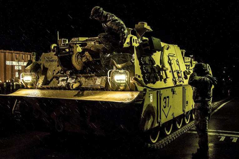 Soldiers and civilians inspect a tank in the dark.
