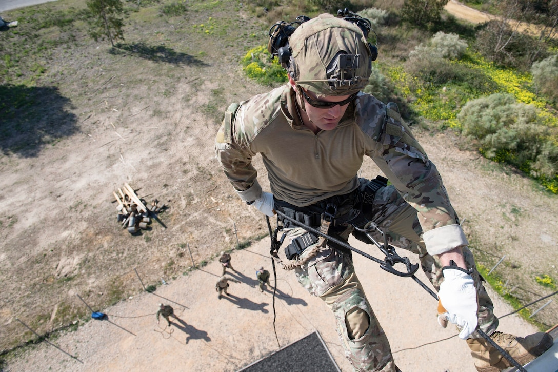 A sailor holds a rope at the top of a tower as service members watch.