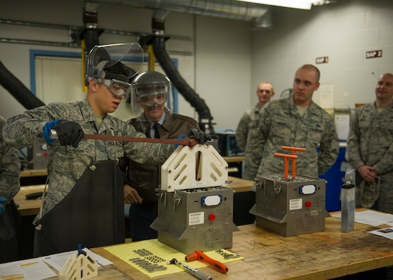 U.S. Air Force Senior Airman Brandon Dinh, 446th Maintenance Squadron (MXS) electrical and environmental technician, demonstrates how to operate a battery cell extracting device to Maj. Gen. Randall Ogden, commander of the 4th Air Force, U.S. Air Force Reserve Command, on McChord Field, Washington, Oct. 6, 2019. The innovative battery cell extractor, designed by members of the 446th MXS, was assembled and tested to provide a safer and more effective workflow when extracting battery cells. (U.S. Air Force photo by Senior Airman Christopher Sommers)