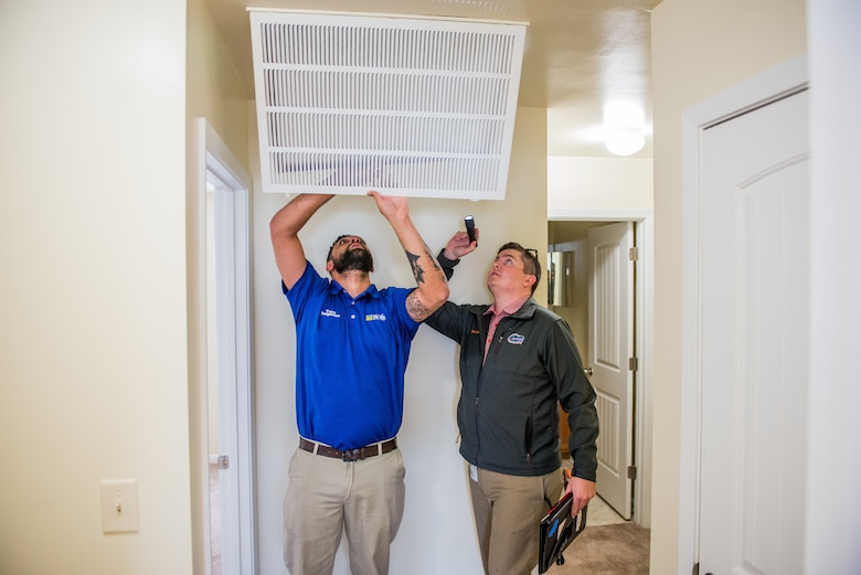 Two men inspect a ceiling vent in a home.