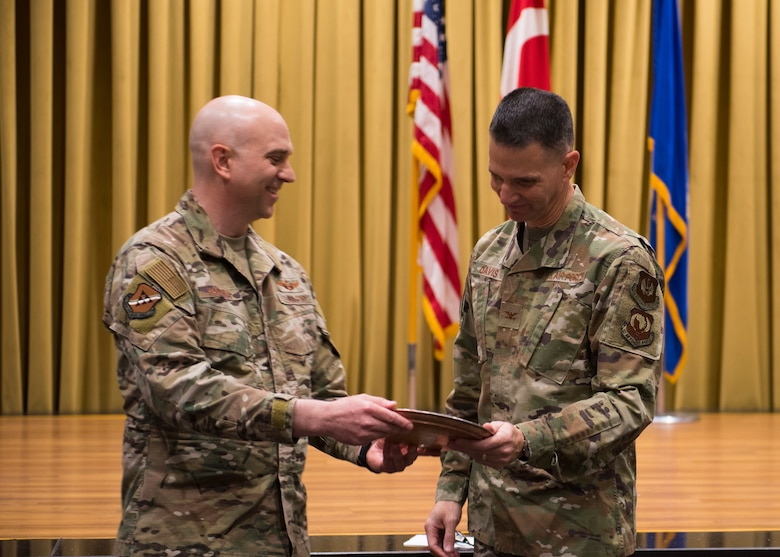 U.S. Air Force Col. John W. Hawkins, 39th Air Base Wing vice commander (left) presents U.S. Air Forces in Europe and Air Forces Africa Command Chaplain Col. Trent Davis (right) with a gift, Feb. 20, 2020, at Incirlik Air Base, Turkey. Both English and Turkish writing was engraved on the copper-plated memento to express appreciation for his words during the 2020 National Prayer Breakfast. (U.S. Air Force photo by Senior Airman Matthew Angulo)