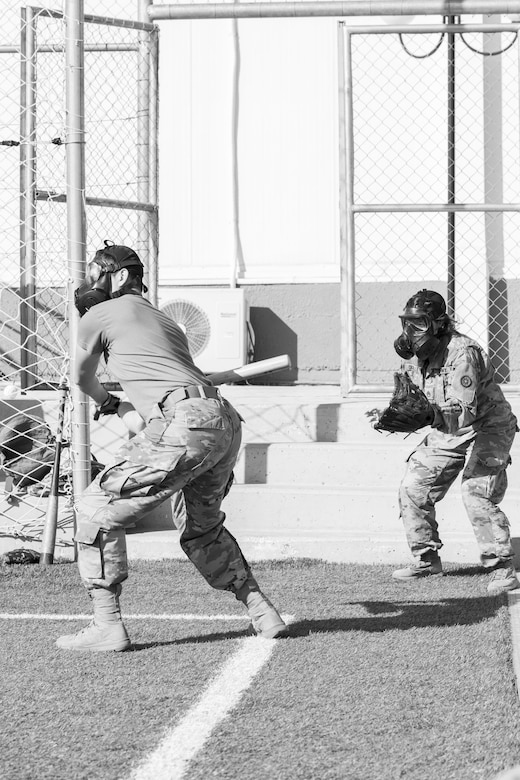 A U.S. Army Soldier, with 655 Regional Support Group, 316 Sustainment Command (Expeditionary), 377 Theater Sustainment Command, prepares to swing at a ball during a game of gas mask baseball Feb. 12, 2020 at Joint Training Center-Jordan, paying tribute to former service members who used the sport to train for chemical warfare during WWI. We still have the greatest Army in the world. We serve the people of the United States and we are going to protect them with our lives if that is what it comes to. (U.S. Army photo by Sgt. 1st Class Shaiyla B. Hakeem)