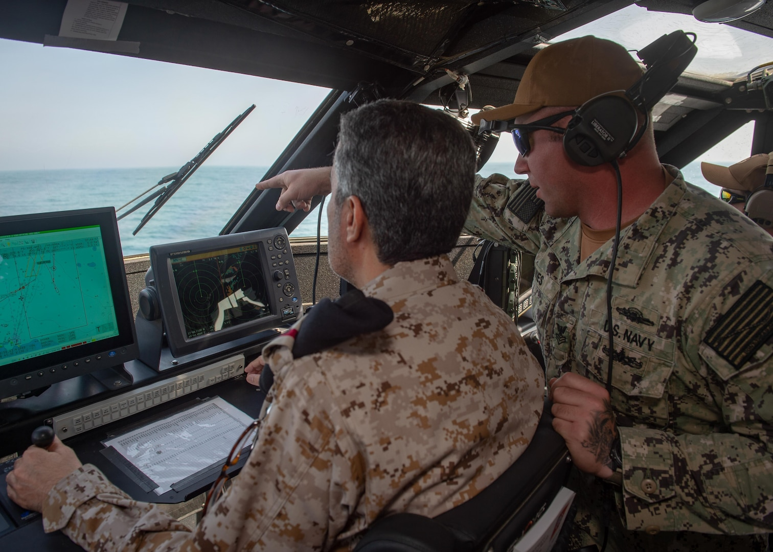 JUBAIL, Kingdom of Saudi Arabia 200223-N-JO908-1073 Gunner's Mate 1st Class Andrew Davies, assigned to Commander Task Force 56, guides Rear Adm. Majed Haz'z Al-Kahtani, Deputy Commander, Royal Saudi Naval Forces (RSNF) Eastern Fleet, on how to operate a Mark VI patrol boat during an underway as part of exercise Nautical Defender 20 in Jubail, Kingdom of Saudi Arabia Feb. 23. ND is a bilateral maritime exercise between the U.S. Navy and the RSNF designed to build and sustain warfighting capabilities, support long term regional security and enhance military-to-military interoperability with the U.S. and Kingdom of Saudi Arabia. (U.S. Navy photo by Mass Communication Specialist 1st Class Kory Alsberry)