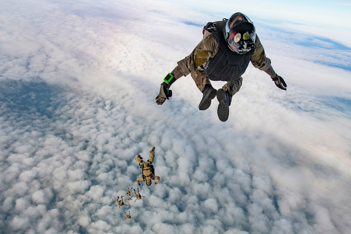 Sailors wearing parachute backpacks descend in a cloud-studded sky.