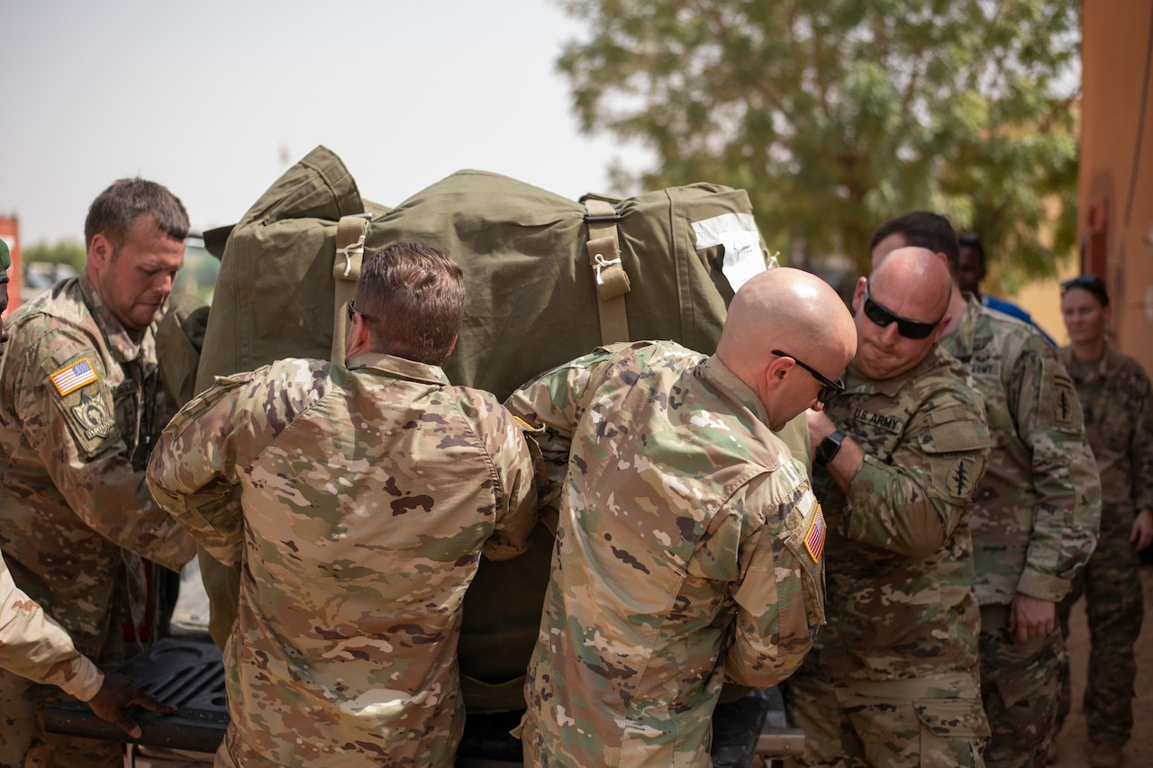 A group of soldiers carry a large bag.