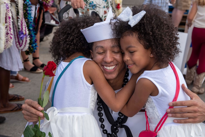 Fire Control Technician 1st Class Quincy Miller, from Savannah, Georgia, assigned to the Virginia-class fast-attack submarine USS Texas (SSN 775), embraces his family during Texas' homecoming. Texas performed a full spectrum of operations, including anti-submarine and anti-surface warfare, during the seven-month Indo-Pacific deployment. (U.S. Navy photo by Chief Mass Communication Specialist Amanda Gray/Released)