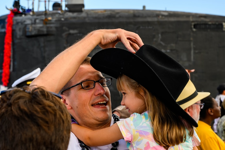Cmdr. Mike Dolbec, from Manchester, New Hampshire, commanding officer of the Virginia-class fast-attack submarine USS Texas (SSN 775), greets his family during Texas' homecoming. Texas performed a full spectrum of operations, including anti-submarine and anti-surface warfare, during the seven-month Indo-Pacific deployment. (U.S. Navy photo by Mass Communication Specialist 1st Class Michael B. Zingaro/Released)