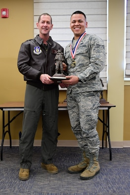Col. John F. Robinson, commander of the 911th Airlift Wing, presents Senior Airman Jeffrey Morales Rosa, client systems technician with the 911th Communications Squadron, with the Airman of the Year award at the Pittsburgh International Airport Air Reserve Station, Pennsylvania, Feb. 8, 2020.