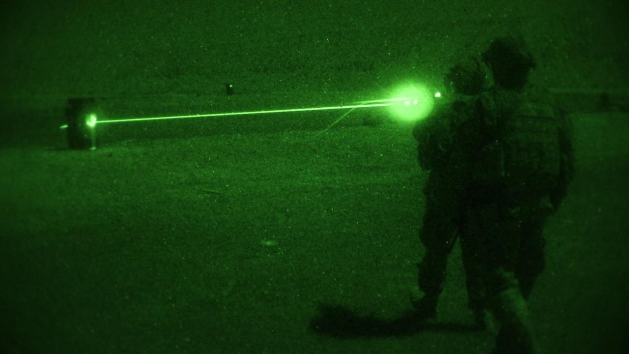 Soldier fires machine gun at night.