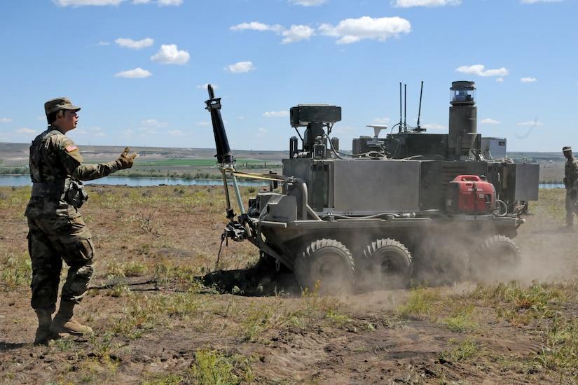 A soldier walks near a wheeled farm vehicle as it crosses a field.