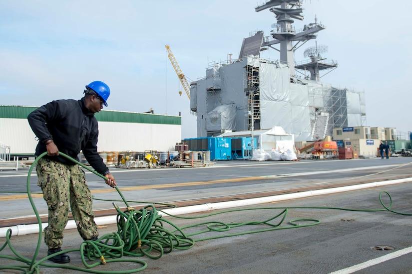 A sailor untangles an air hose.
