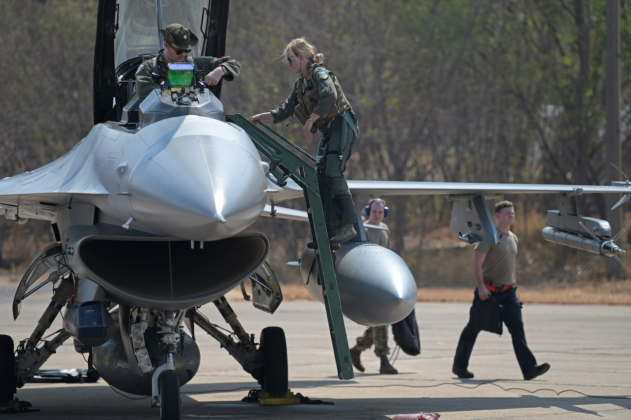 Airmen work on a jet as it sits on a runway.