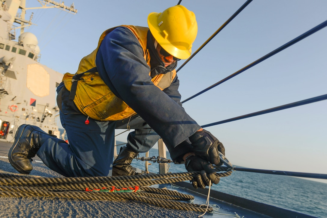 A sailor wearing a yellow hard hat and vest cuts a rope.