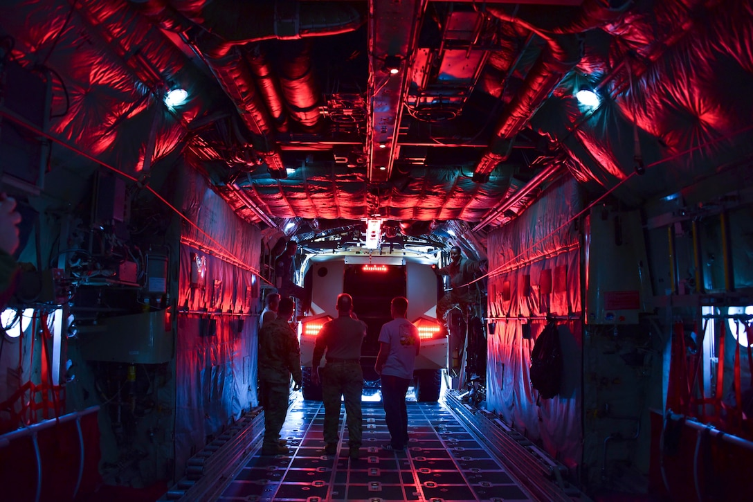 Airmen stand in an area illuminated by a red light.