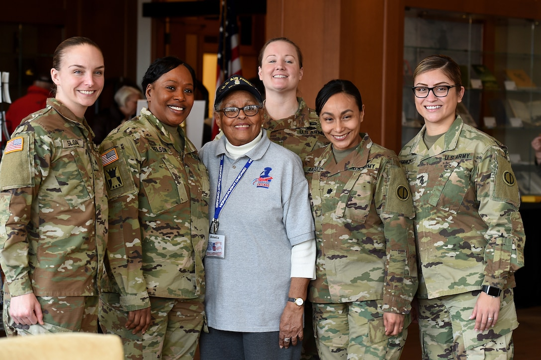 Amelia Cunningham, U.S. Air Force veteran, pauses for a photo with Army Reserve Soldiers, assigned to the 85th U.S. Army Reserve Support Command, during the Operation HerStory all-female Honor Flight news conference at Pritzker Military Library, in Chicago, February 25, 2020.