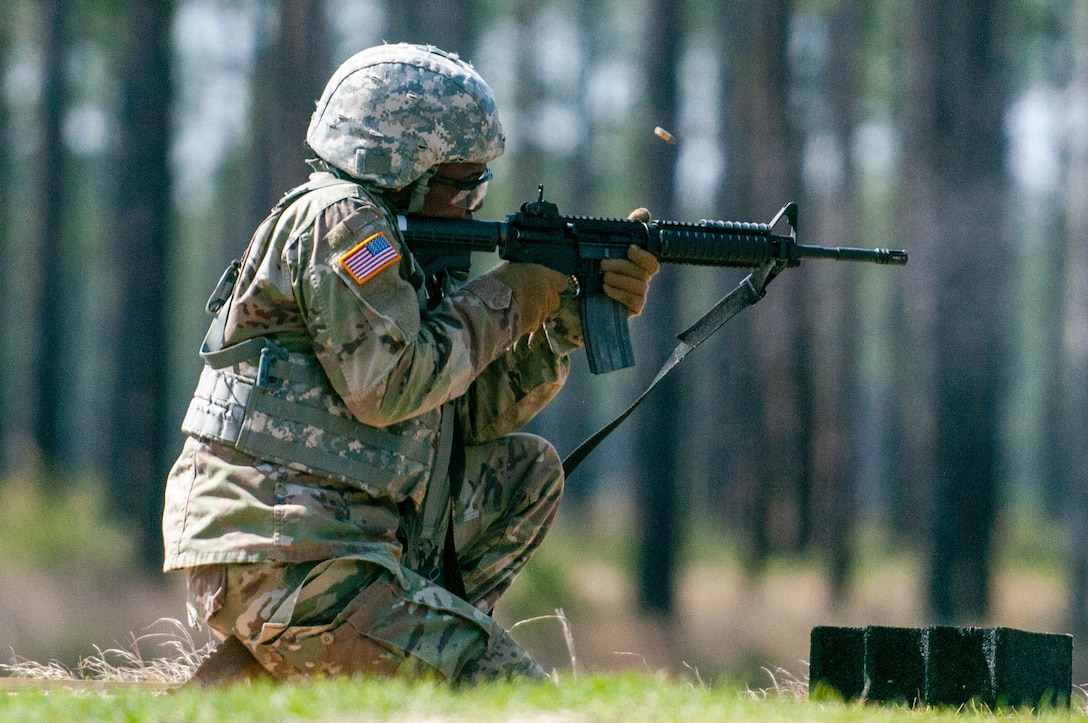 A soldier kneels on one knee outdoors and fires a weapon.