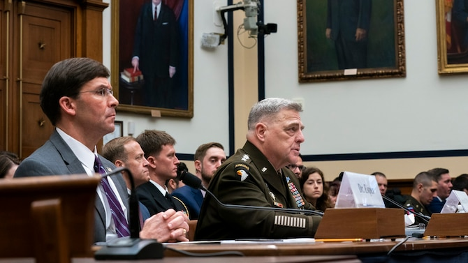 Army Gen. Mark A. Milley sits and speaks at a table.
