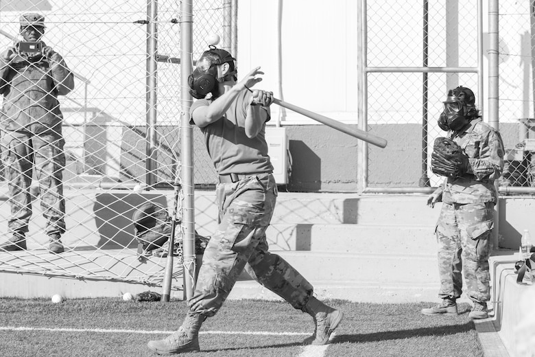 A U.S. Army Soldier, with 655 Regional Support Group, 316 Sustainment Command (Expeditionary), 377 Theater Sustainment Command, swings at a ball during a game of gas mask baseball Feb. 12, 2020 at Joint Training Center-Jordan, paying tribute to former service members who used the sport to train for chemical warfare during WWI. We still have the greatest Army in the world. We serve the people of the United States and we are going to protect them with our lives if that is what it comes to. (U.S. Army photo by Sgt. 1st Class Shaiyla B. Hakeem)