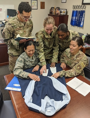 SAs Jessica Sunkamaneevongse, seated left, and Alexandra Garced, seated right, and Air University Squadron Officer School classmates discuss how to redesign the Air Force maternity uniform. (Photo by AU/PA)