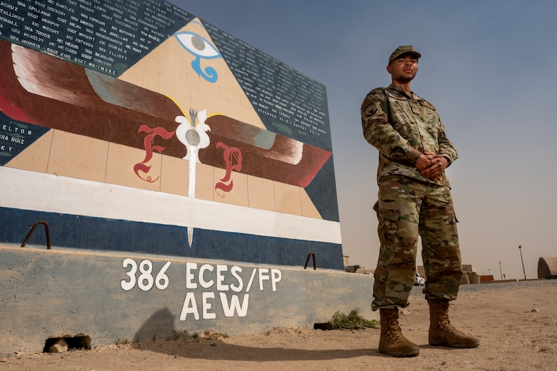 Airman Antwain Hanks, 386th Expeditionary Civil Engineer Squadron force protection, poses for a photo in front of an FP mural at Ali Al Salem Air Base, Kuwait, Feb. 26, 2020. Hanks is originally a photojournalist from the 366th Fighter Wing Public Affairs office at Mountain Home Air Force Base, Idaho. (U.S. Air Force photo by Senior Airman JaNae Capuno)