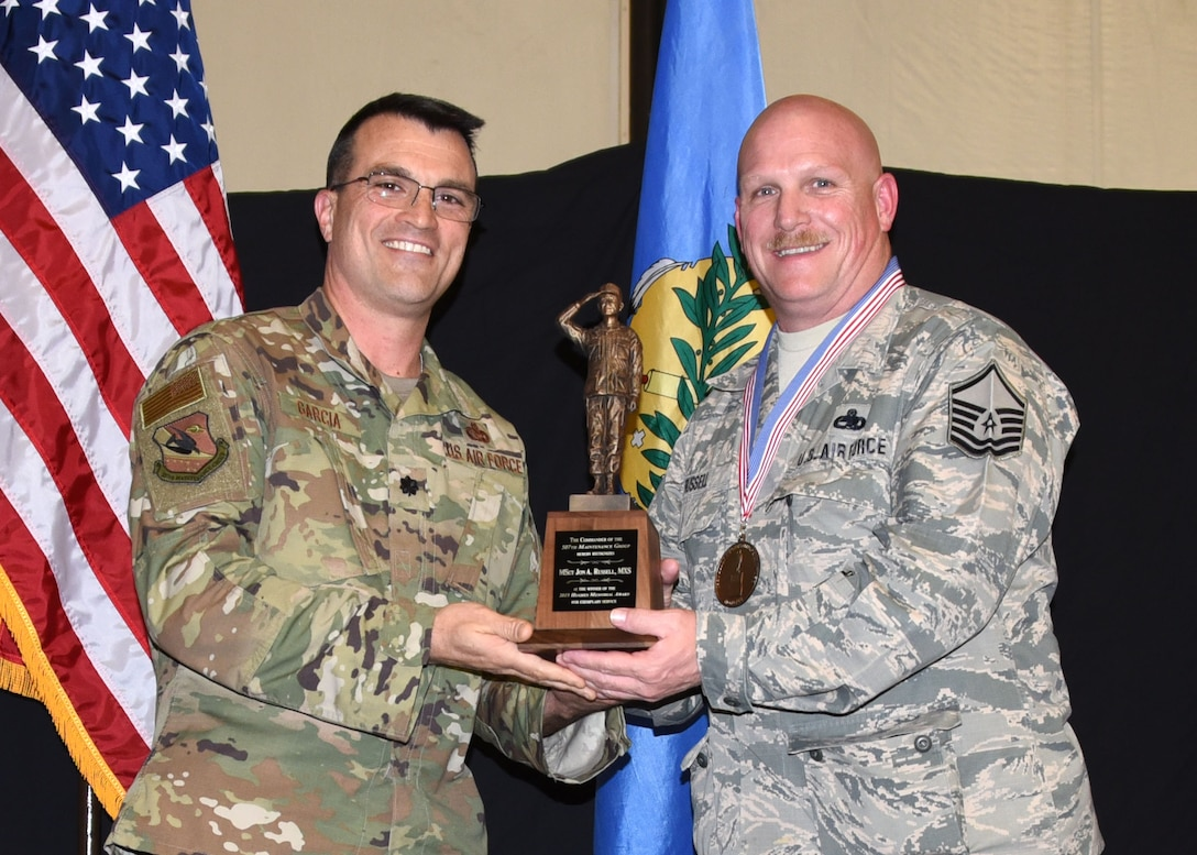 Master Sgt. Jon Russell, 507th Maintenance Squadron, receives the 2019 507th Maintenance Group Billy Hughes Memorial Award from Lt. Col. Bradley Garcia, 507th MXG vice commander, during the 2019 Annual Awards Banquet Feb. 8, 2020, at Tinker Air Force Base, Oklahoma. (U.S. Air Force photo by Tech. Sgt. Samantha Mathison)