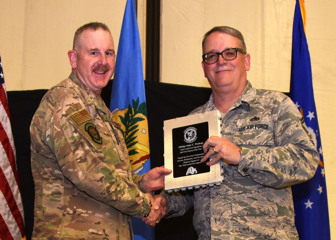 Senior Master Sgt. John Prokup, 507th Aerial Port Squadron, receives the 2019 Port Dawg of the Year award from Lt. Col. Darryl McLean, 72d APS commander, during the 2019 Annual Awards Banquet Feb. 8, 2020, at Tinker Air Force Base, Oklahoma. (U.S. Air Force photo by Tech. Sgt. Samantha Mathison)