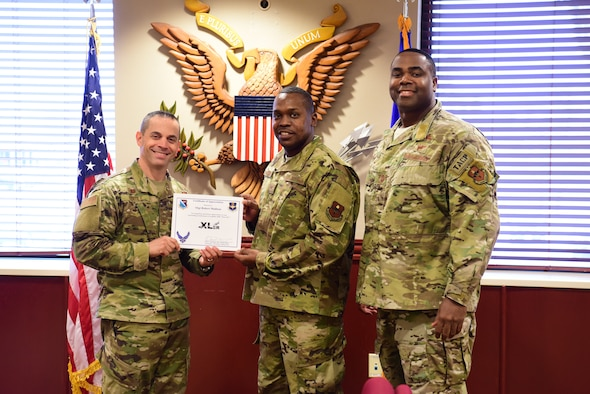 "Staff Sgt. Robert Madison, 47th Flying Training Wing NCO in charge of wing administration, accepts the ""XLer of the week"" award from Col. Lee Gentile, the 47th Flying Training Wing Commander, and Chief Master Sgt. Robert L. Zackery III, 47th FTW command chief master sergeant, on Feb. 14, 2020 at Laughlin Air Force Base, Texas. The ""XLer of the Week"" award is given to those who consistently make outstanding contributions to their unit and the Laughlin mission. (U.S. Air Force photo by Senior Airman John A. Crawford)"