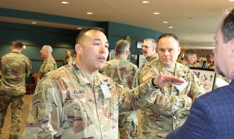 Chief Warrant Officer 3 Jason Flores (left), an Unmanned Aerial Systems (UAS) warrant officer with the 2nd Infantry Division, Fort Carson, Colorado,  discusses UAS operations during a break at the AMCOM 101 for Aviation forum, Feb. 19-20. Several aviation support activates manned information booths in the break area for Soldiers to interact and get answers to specific questions.