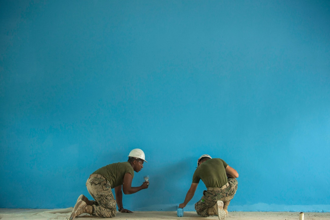 Two Marines paint a wall turquoise blue.