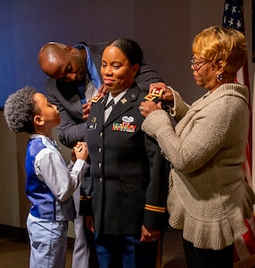 Husband Chris Price, son Jeremiah and mother, Doris Dorsey, pin the rank of Lieutenant Colonel on Danielle Price during a ceremony Feb. 27 at the Illinois State Military Museum, Springfield, Illinois.