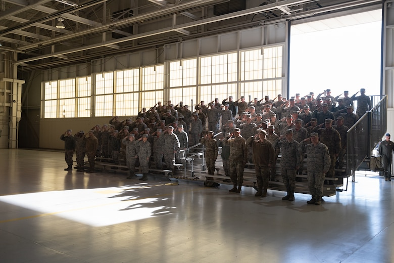 A group of Airmen salutes at a ceremony