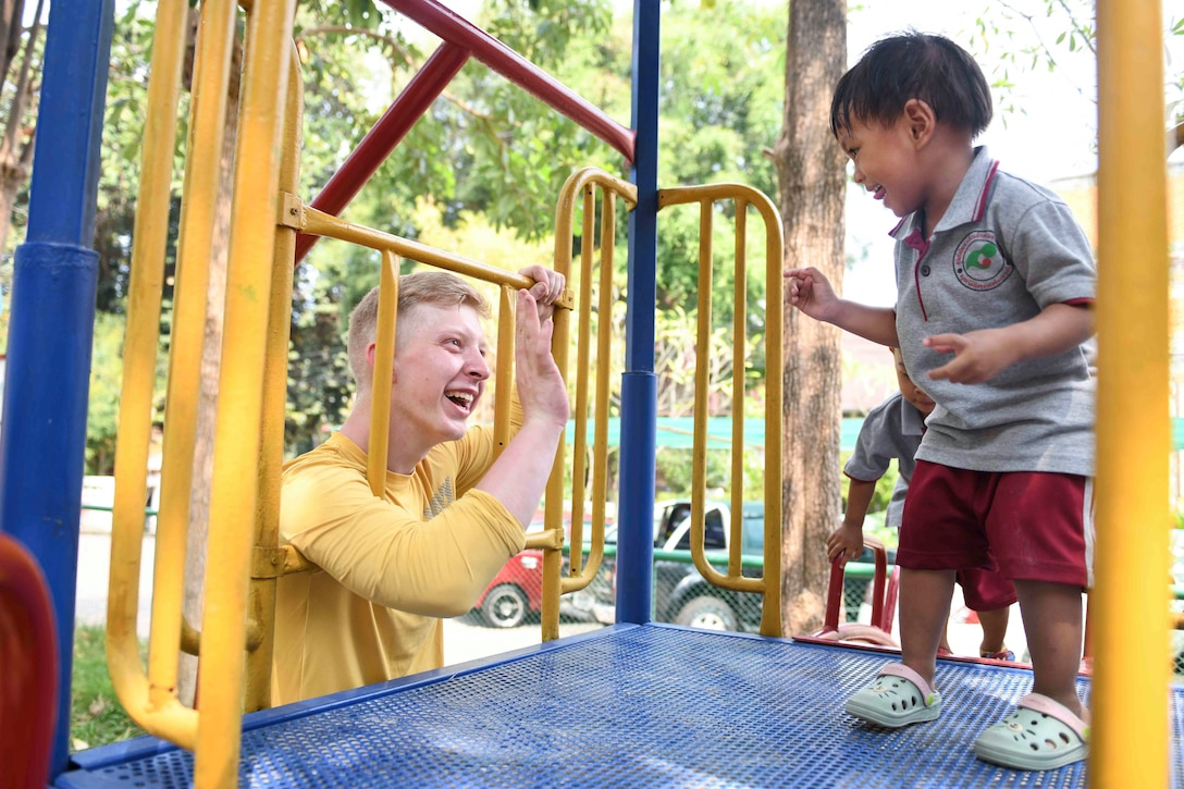A sailor smiles at a child standing on playground equipment and the child smiles back.