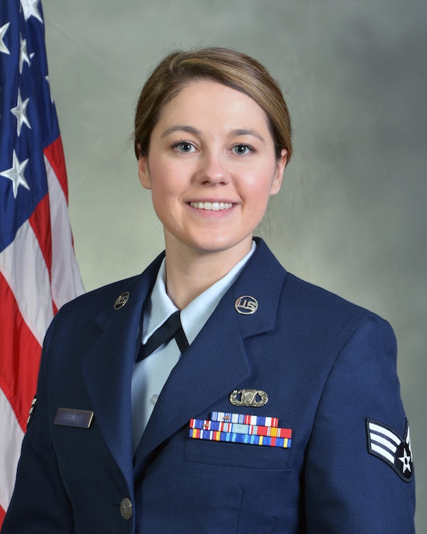 head and shoulders of military woman in uniform, gray background and U.S. flag over her right shoulder
